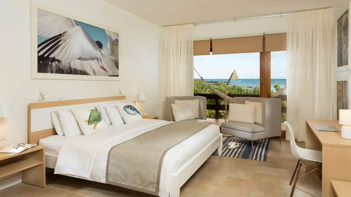 Finch Bay Eco Hotel room with large bed, large windows with ocean view and chairs.