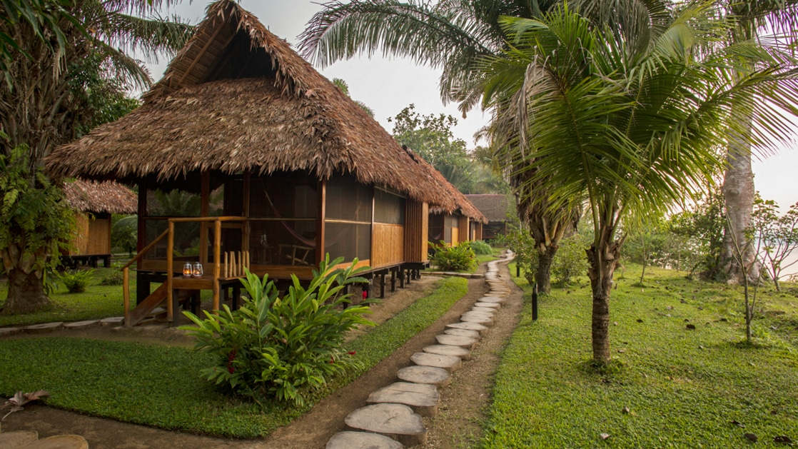 The exterior of a cabana hut at Inkaterra Reserva Amazonica with a thatched roof and covered patio. The eco-luxury lodge has four cabana options, with authentic, tall fishtail palm rooftops and indigenous architectural design.