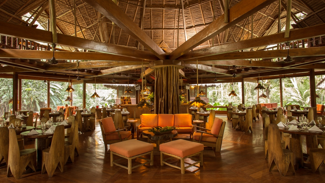 The dining room at Inkaterra Reserva is inspired by the tropical flavors of the Amazon region, with a tree trunk beam as the centerpiece, wood thatched roof and all wood carved tables and chairs.