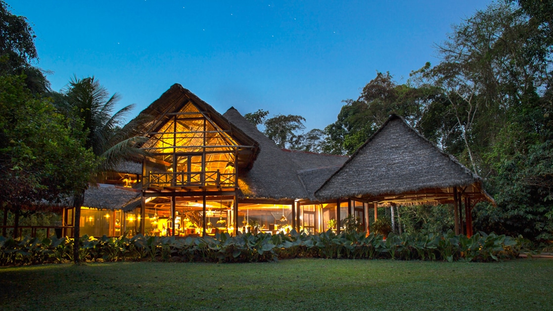 The exterior of the Inkaterra Reserva Amazonica at night, with thatched roofs and lights. It is an eco-luxury lodge in the heart of the Peruvian Amazon Rainforest, adjacent to the Tambopata National Park