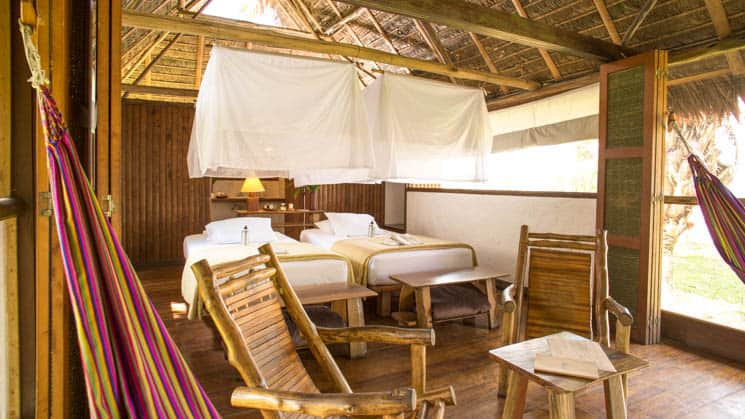 Inkaterra Superior room with beds, chairs and mosquito nets.