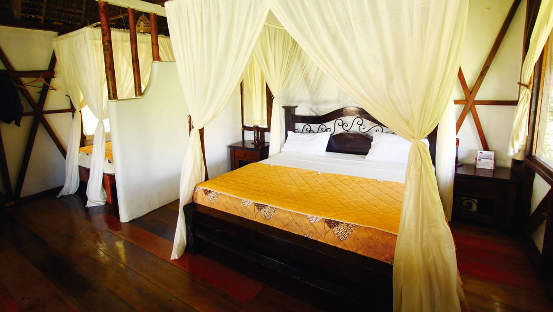 Napo Wildlife Center cabana room with four-posted large bed with additional bed.