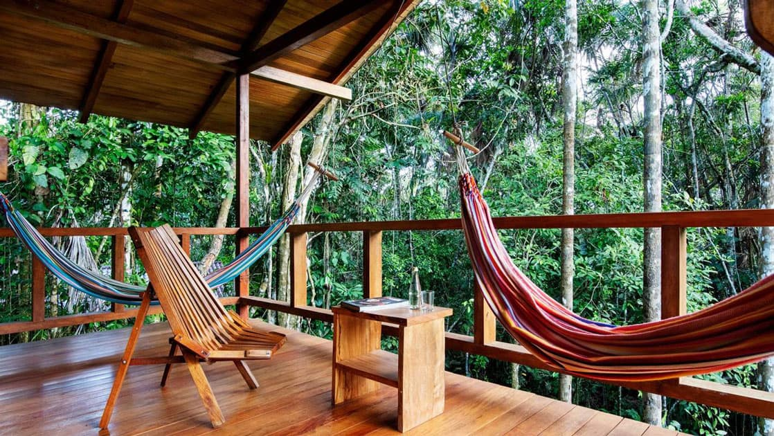 Private balcony at Sacha Jungle Lodge, with wooden floors & railing, 2 brightly-colored hammocks, wooden chair & book on a small table.