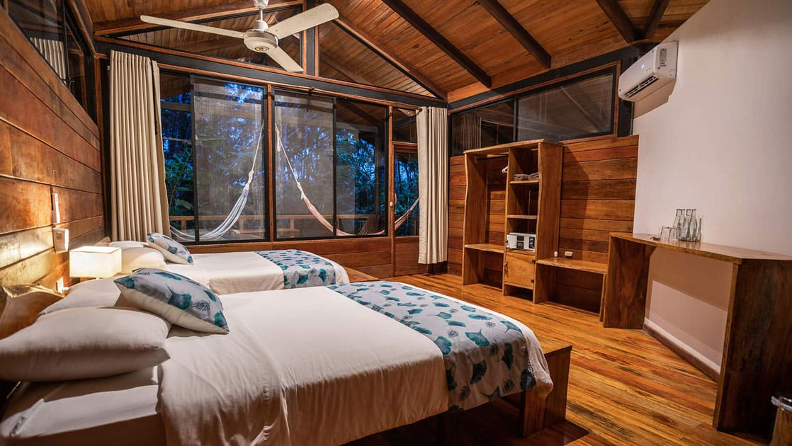 Standard Cabin at Sacha Jungle Lodge with wooden floors, white & teak walls, air conditioning unit, jungle-themed bedding on 2 twin beds & large windows plus door opening onto private balcony.