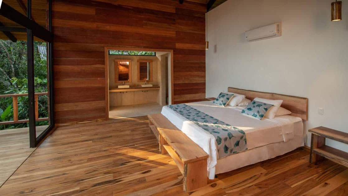 Suite at Sacha Jungle Lodge with wooden floors, white & teak walls, air conditioning unit, bathroom with dual sinks, jungle-themed bedding on double bed & floor-length windows opening onto private balcony.