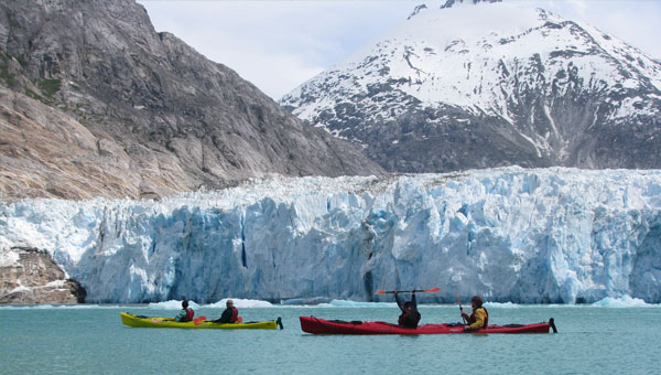Yellow and red double kayaks in front of a glacier in Alaska