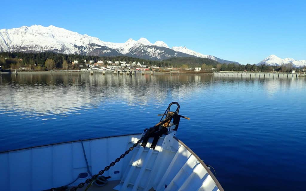 The bow of the Wilderness Adventurer ship coming in to port in Haines with blue skies and snowy mountains.