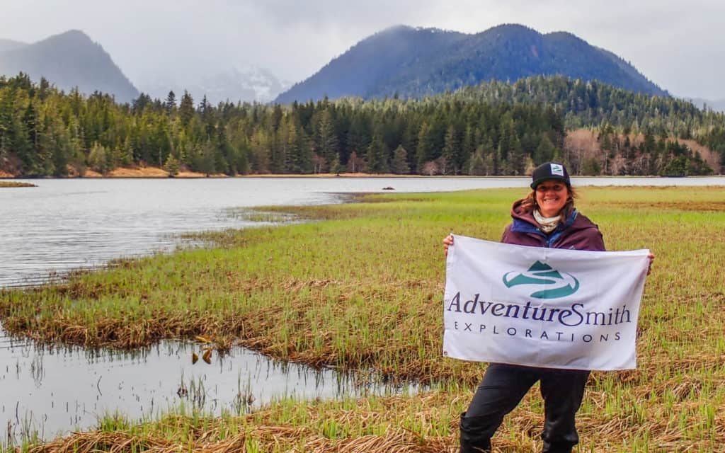 An AdventureSmith traveler with flag in front of a lake and mountains in Alaska.