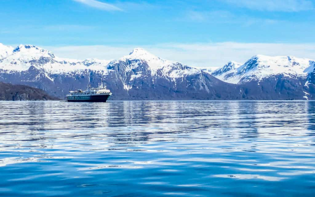 Wilderness Adventurer small ship sailing in Alaska in calm waters with snow mountains behind.