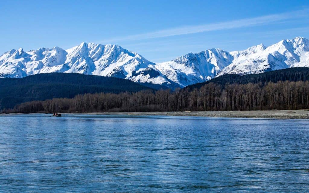 A raft floating down the Alaska river the Chilkat with the snowy Chilkat Mountain Range behind.