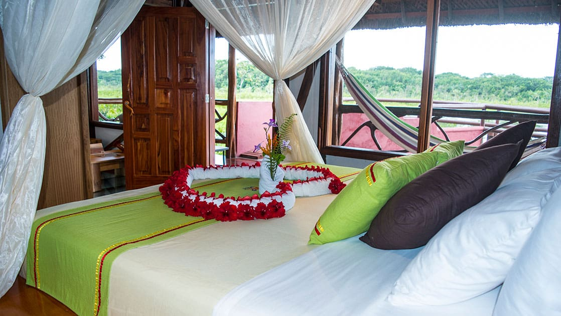 Napo Wildlife Center panoramic suite withe large bed decorated with flowers and panoramic windows.
