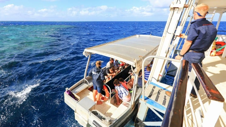 adventure travelers load a skiff from a small ship on a sunny day during the great barrier reef australia cruise