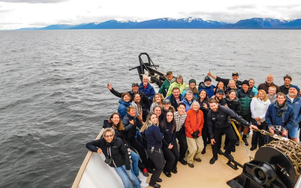 A group of Alaska travelers on the bow of the Wilderness Adventurer smiling for the camera at the end of a small ship cruise through alaska.
