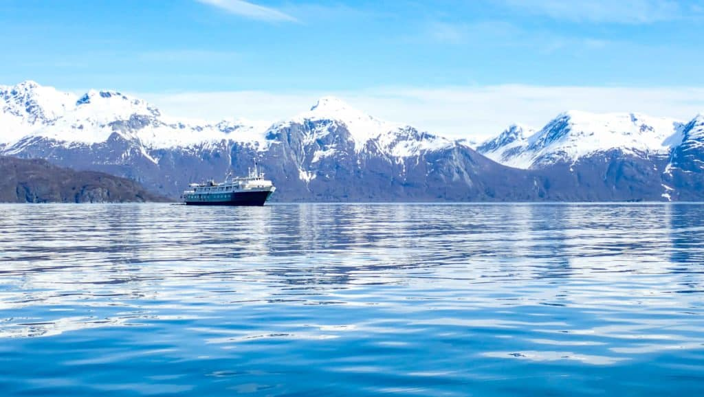 A reflection on the blue water of the snow capped mountain range and the alaska small ship -wilderness adventurer floating on the horizon