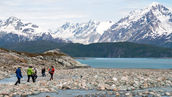 Alaska travelers hike on a rocky shoreline with ocean and snowy mountains