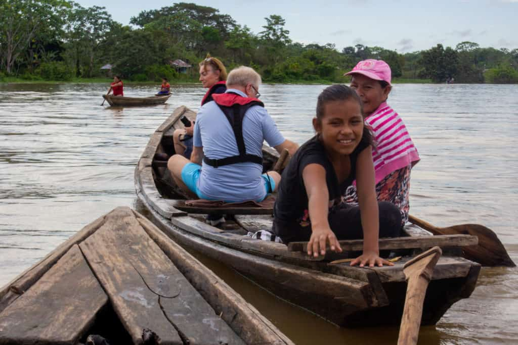 Amazonian people and travelers aboard a dugout canoe in the Amazon.