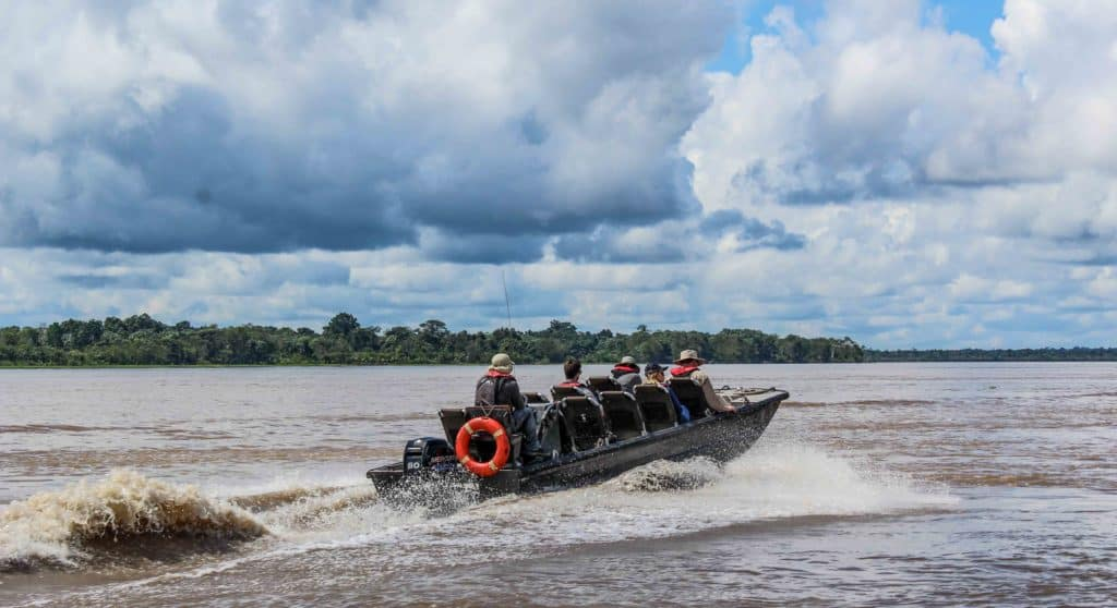 A skiff tour in the Amazon in wide open waters with land and clouds behind.