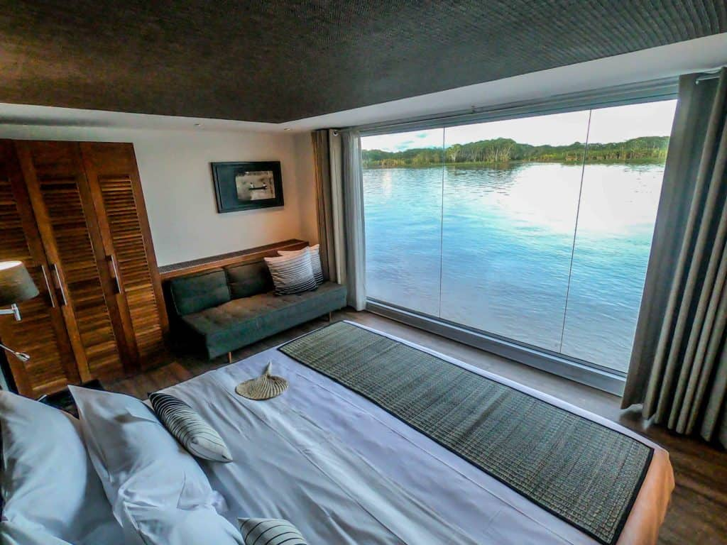 A cabin aboard the Aria with floor to ceiling windows, couch, closet and king sized bed.