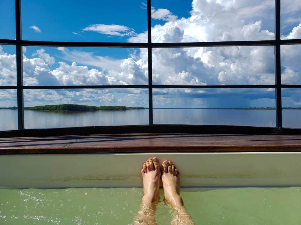 Feet on the edge of the cold-water plunge pool aboard the Aria looking out over clouds and an island.