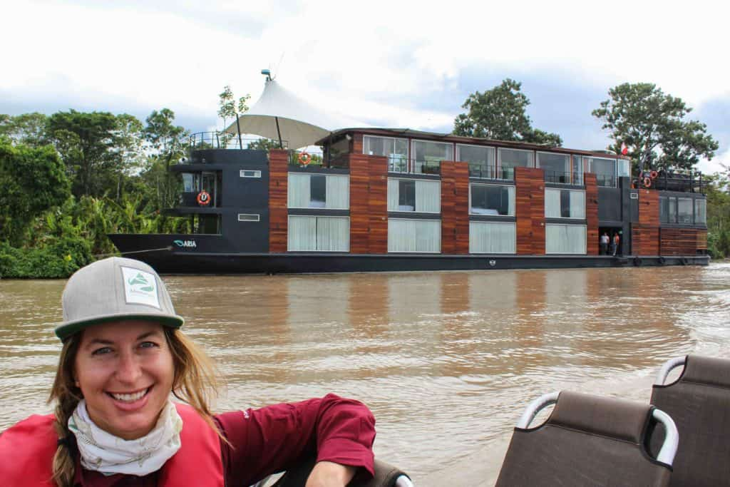 Adventure Specialist Taylor Cranney smiling on a skiff in front of the Aria cruise ship in the Peruvian Amazon.