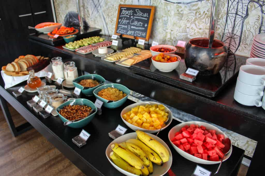 A breakfast spread aboard the Aria with fruits, bread, cheese, cereal and rice pudding.