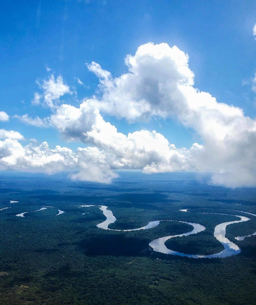 The Peruvian Amazon from above winding along through dense forest and fluffy clouds.
