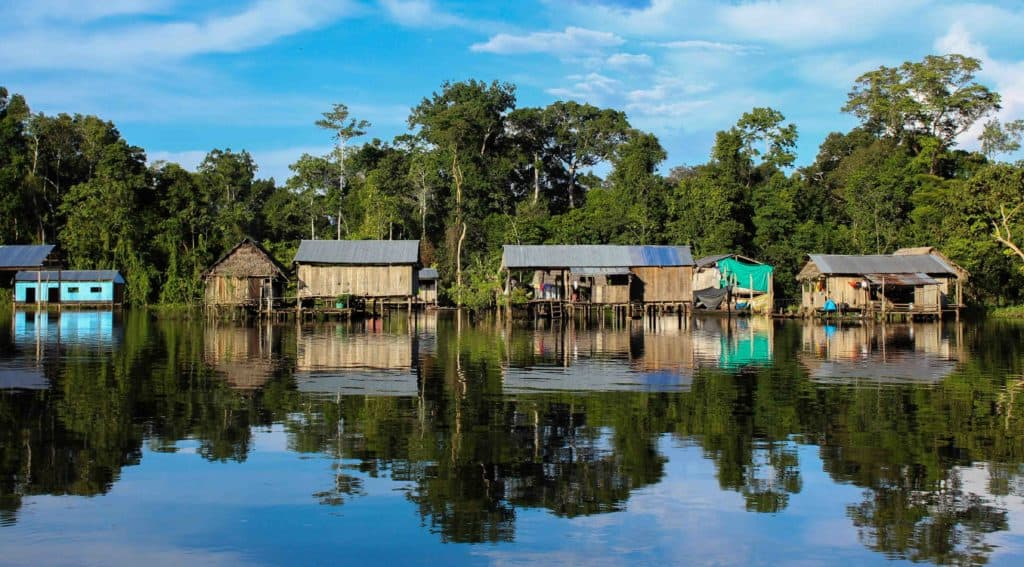A village in the Amazon on stilts with the jungle behind.