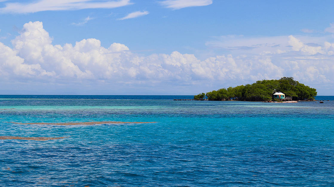 Deep blue and turquoise water surrounding a small island with blue sky on a sunny day
