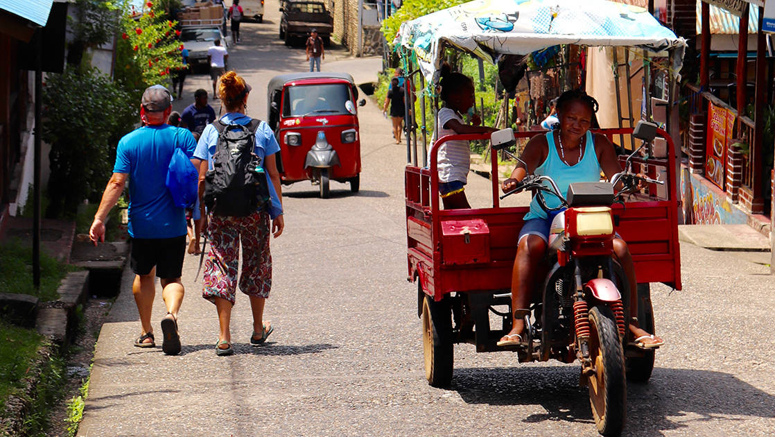 busy street with pedestrians and tuk tuks in livingston, guatemala on a sunny day