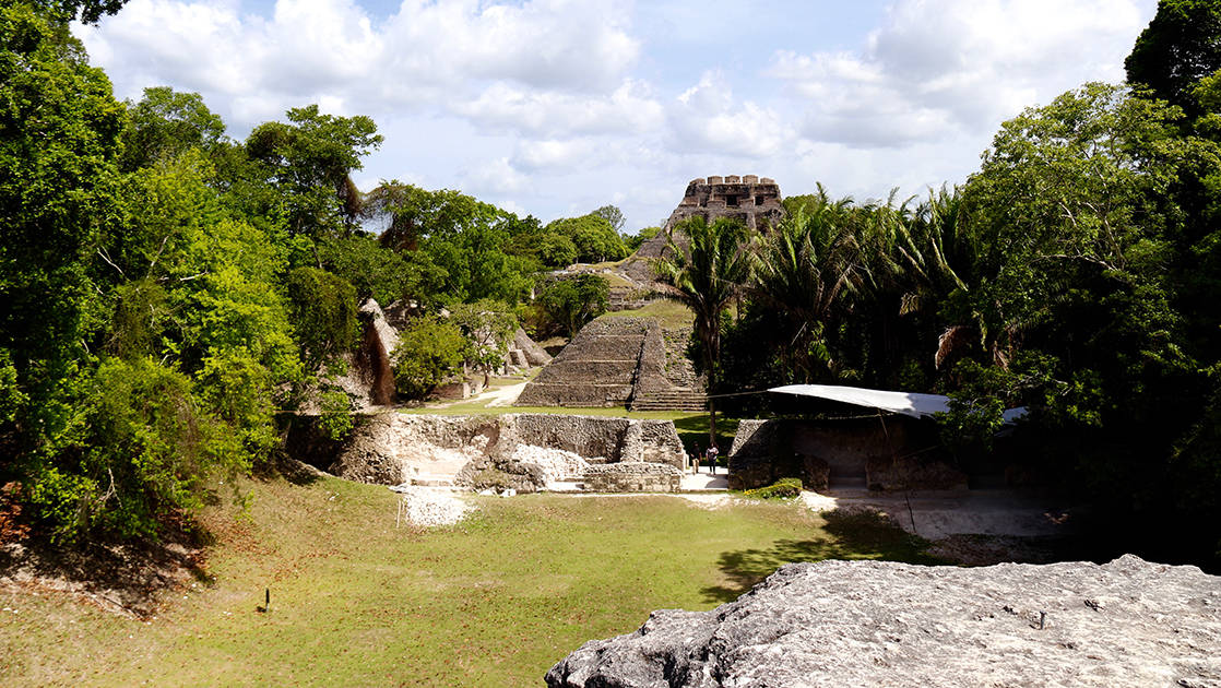 mayan ruins among green grass and trees on a sunny day
