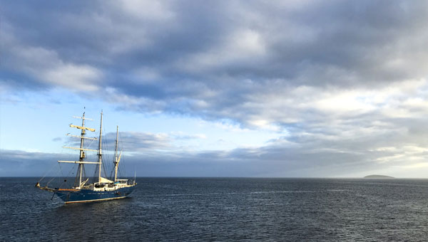 Galapagos sailboat cruises towards the horizon with a cloudy sky at sunset