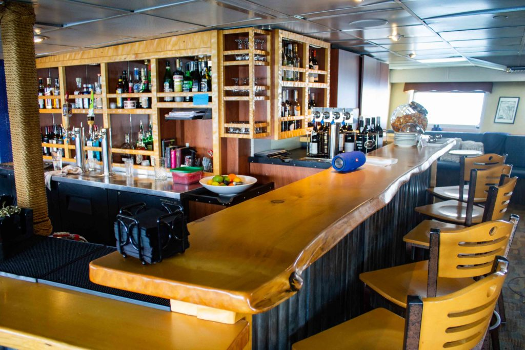 a photo of the bar aboard Wilderness Adventurer, showing glossy wooden counter tops with, wooden high chairs,  cubbyholes are full of spirits, alcohol and other beverage choices