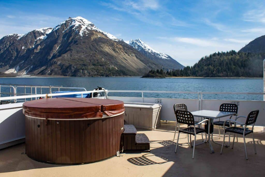 the top deck of small ship Wilderness Adventurer an outdoor table and chairs are set beside a covered Jacuzzi, in the distance a jaged snow capped mountain range end where the water line begins