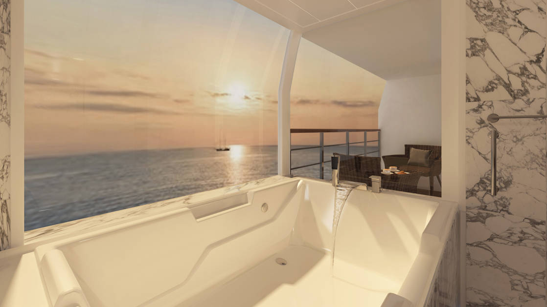 Large white tub with picture window and view on to private balcony of the Bridge Deck Balcony Suite aboard Coral Geographer