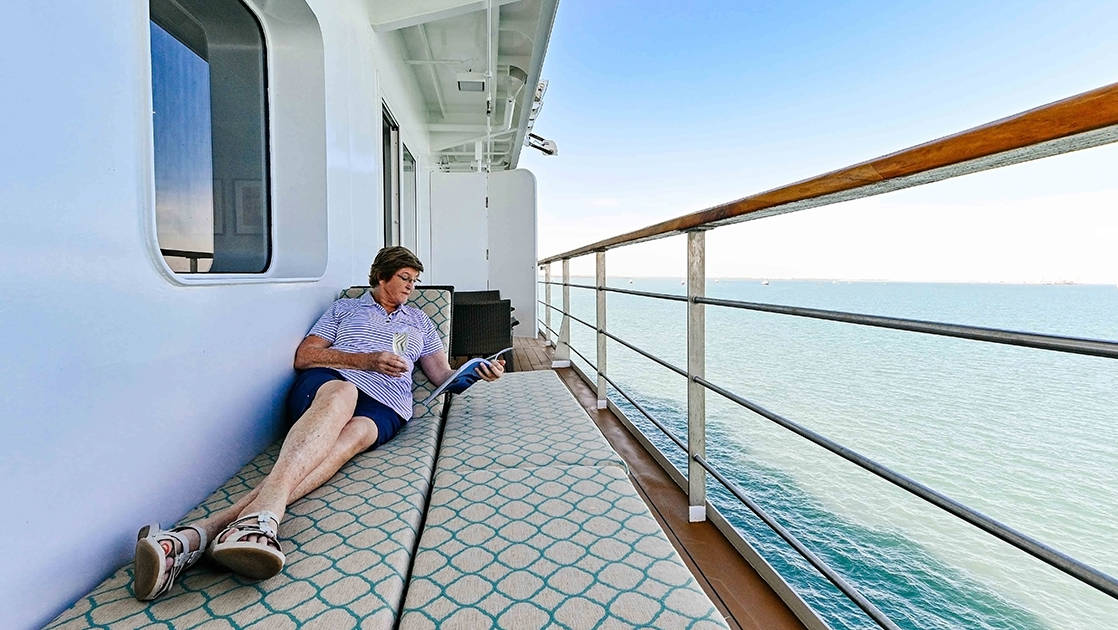 Woman reclining and reading a book on Bridge Deck Balcony Suite's large balcony aboard Coral Geographer small ship.