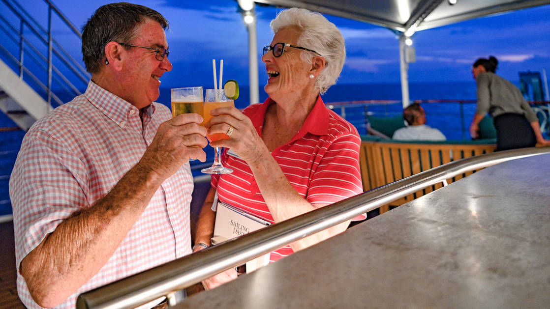 Two guests making an evening toast at a bar with cocktails on the Bridge Deck of the small ship Coral Geographer.
