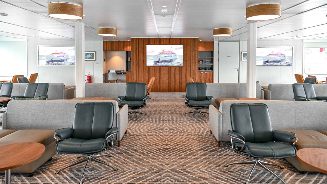Lecture room & lounge aboard Coral Geographer with dark blue and tan modern chairs and couches & TV screens.