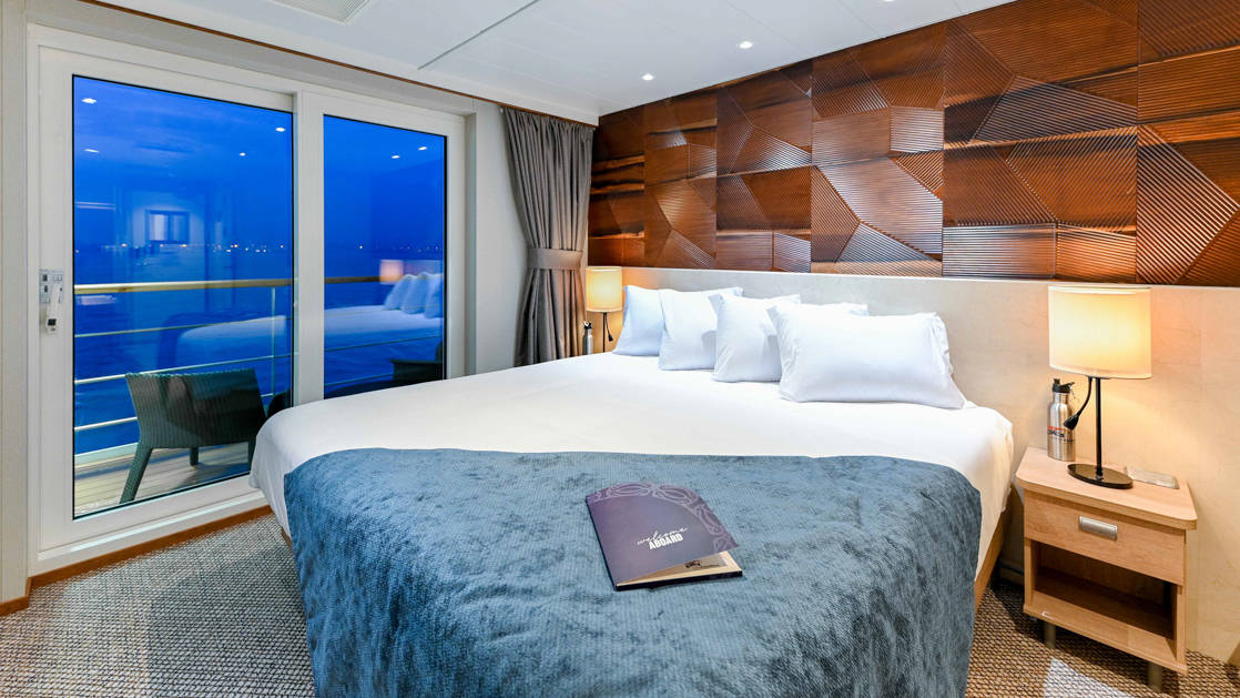 Junior king bed with white linens and blue throw blanket, wooden motif wall behind, sidetable with lit lamp & sliding glass doors to private balcony aboard Coral Geographer ship.