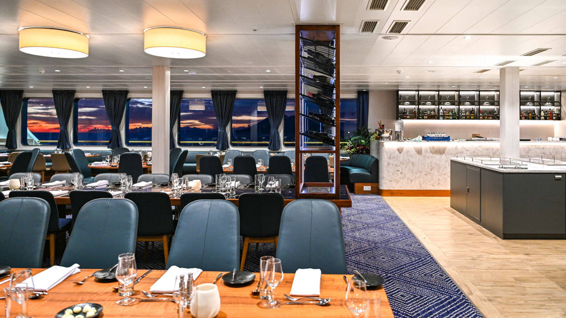 Dining room with long communal table & smaller wooden tables, marble buffet area & tall wine rack aboard small ship Coral Geographer.