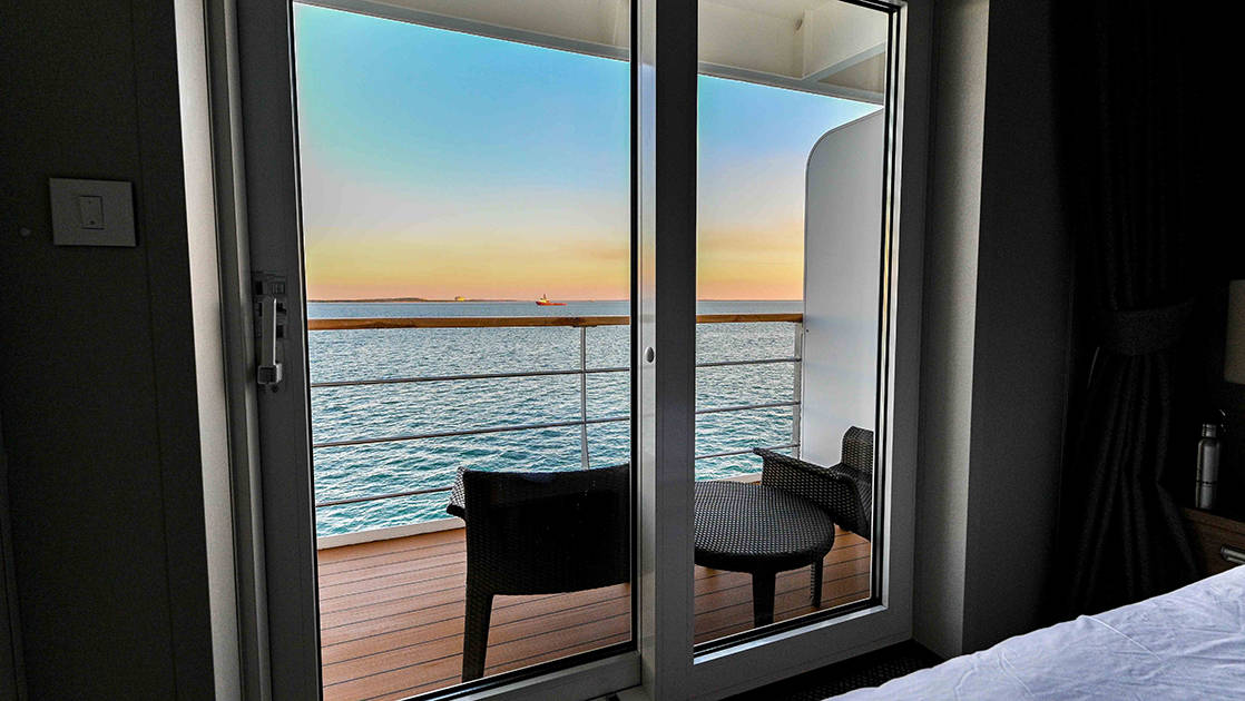 Private balcony with two chairs looking out over a colorful sunset aboard Coral Geographer small expedition ship.