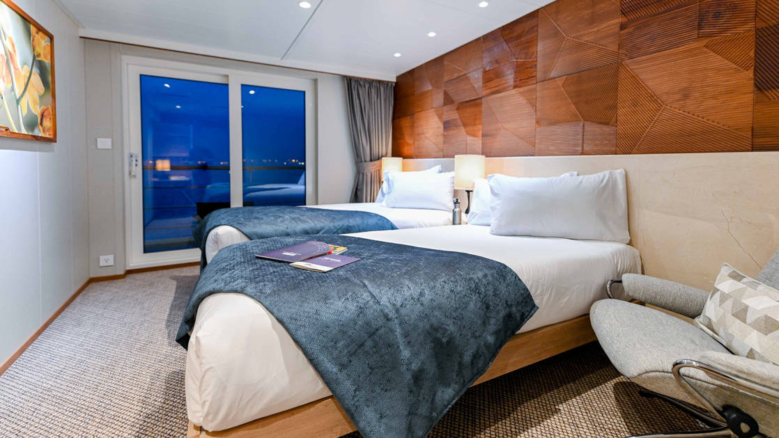 Two twin beds with white linens & blue throw blankets, grey side chair, artwork hanging & sliding glass doors to private balcony aboard Coral Geographer Australia ship.