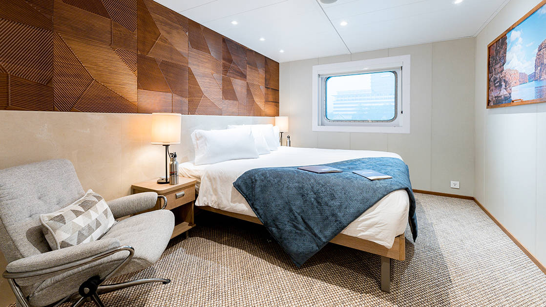 Promenade Deck Stateroom aboard Coral Adventurer small ships with chair, bed, and window.