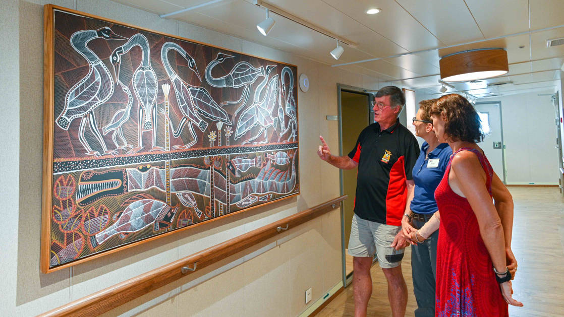 Travelers admire authentic Australian aboriginal painting in the hallway aboard Coral Geographer expedition vessel.