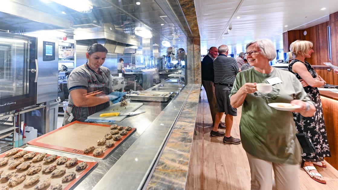 Guest admires view into kitchen as baker prepares cookies in galley aboard Australian ship Coral Geographer.