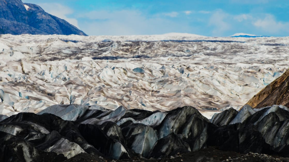 Large white-amd-black glacier with snow and silt and snowcapped mountains in the background on a sunny day in Alaska.
