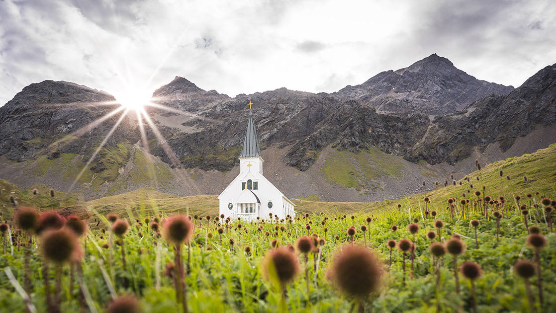 White church sitting in a field of bright green grasses and brown flowers with jagged mountain peaks in the background on a cloudy day with sun in Antarctica.