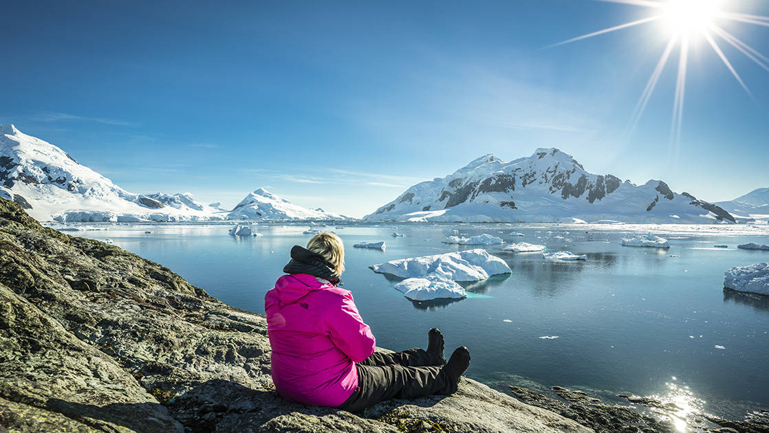 Woman sitting on shoreline in Antarctica with calm ocean, icebergs and snowcapped mountains in the background, on a sunny day.