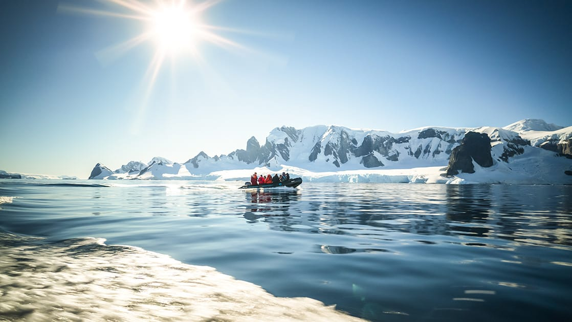 Antarctica travelers on a Zodiac cruise in calm waters with snowy mountains in the background, on a sunny day.