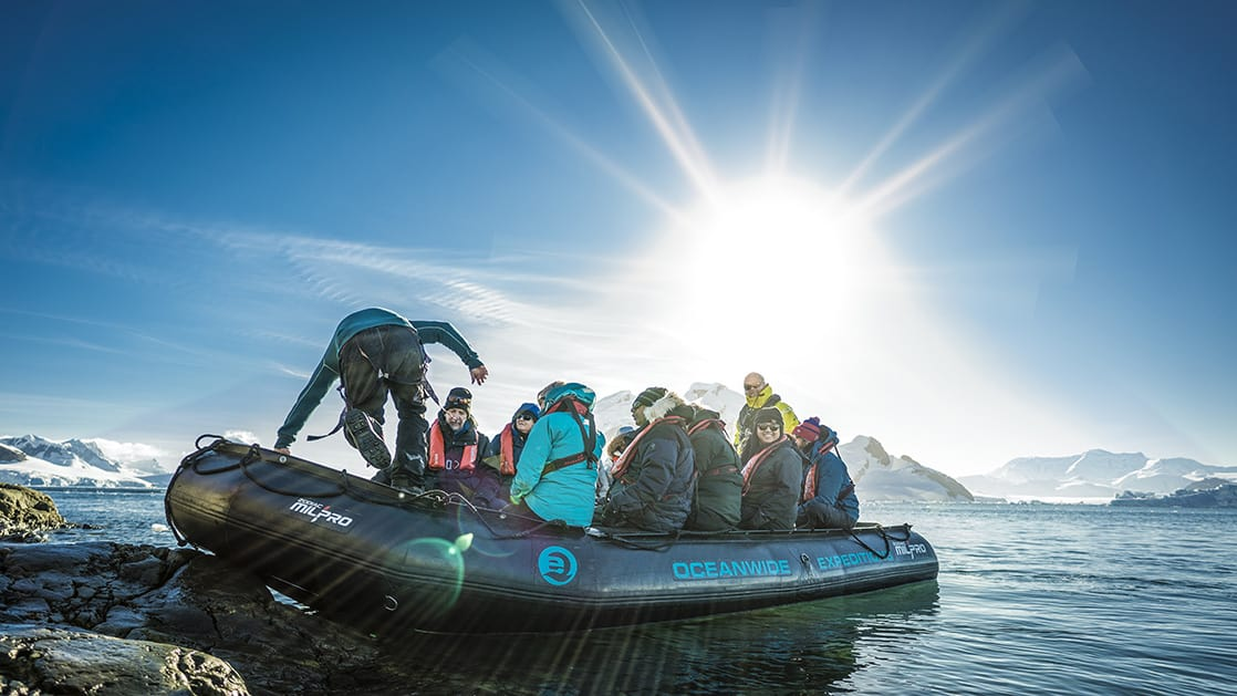 Antarctica travelers landing on shore in a Zodiac on a sunny day.