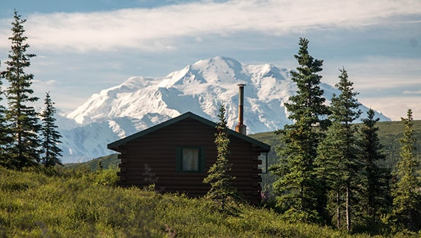 A small Denali National Park log cabin with the snowy Denali peak behind it